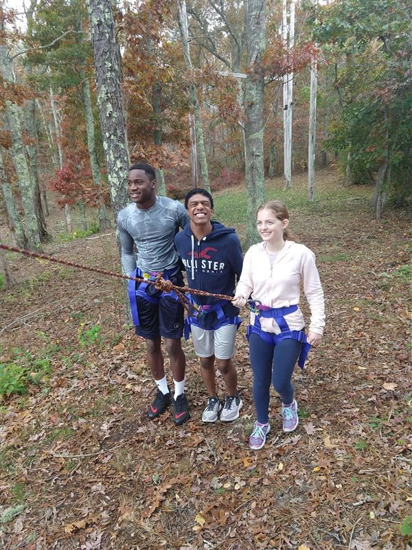Three students demonstrating blog belay in adventure education