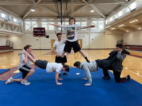 Students performing a group balance