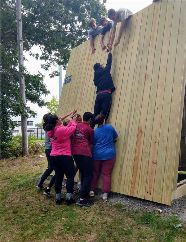 Students assisting a classmate up the free standing low wall in adventure education