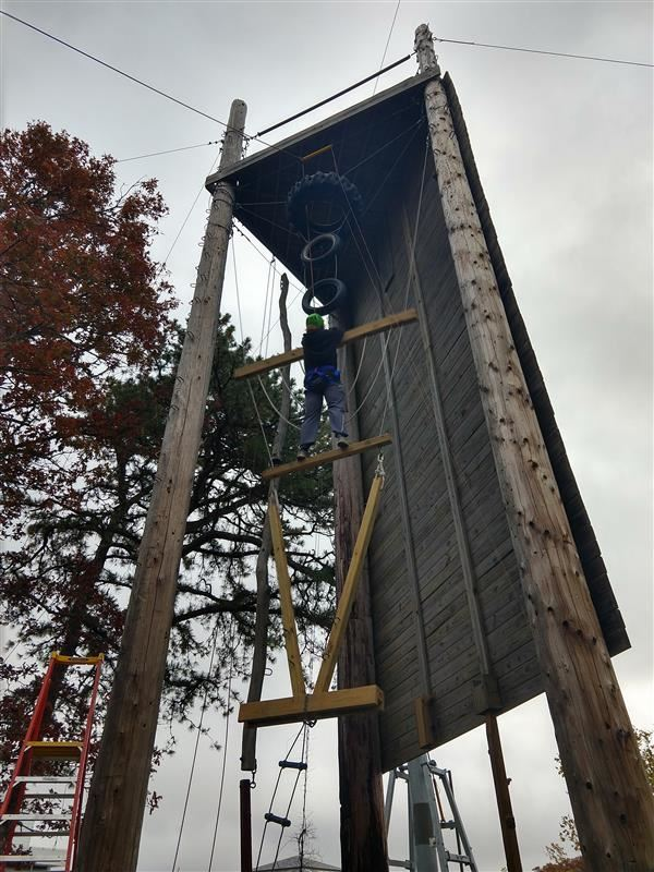 Student climbing on the vertical play pen in adventure education