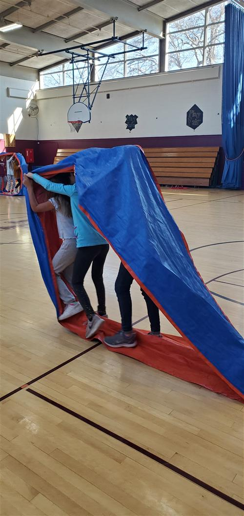 3 students working together to move a tarp