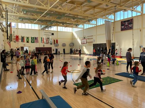 Many students in the Mullen-Hall gymnasium rotating around stations during their fitness day